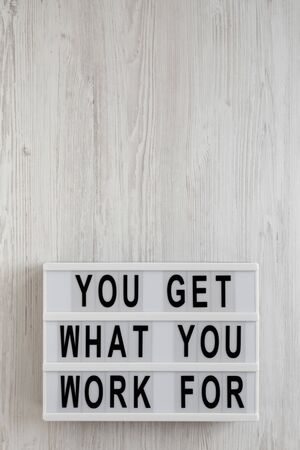 'You get what you work for' words on a modern board on a white wooden background, overhead view. Top view, from above, flat lay. Copy space.