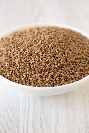 Uncooked Roasted Buckwheat in a white bowl, side view. Close-up. Zdjęcie Seryjne