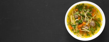 Homemade Sopa a La Minuta in a white bowl on a black background, top view. Flat lay, overhead, from above. Copy space.