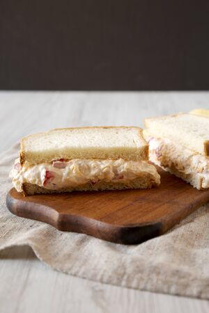 Delicious Homemade Pimento Cheese Sandwich with chips on a rustic wooden board, low angle view. Close-up.