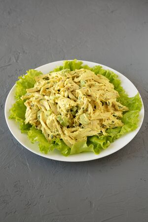 Homemade Coronation Chicken Salad on a white plate on a gray surface, low angle view. Close-up. Stockfoto