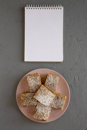 Homemade Tasty Applesauce Cake on a pink plate, blank notepad on a gray surface, top view. Flat lay, overhead, from above. Standard-Bild