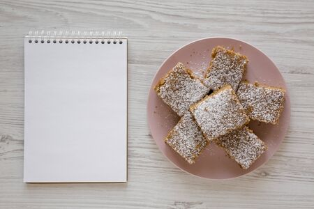 Homemade Tasty Applesauce Cake on a pink plate, blank notepad on a white wooden surface, top view. Flat lay, overhead, from above.