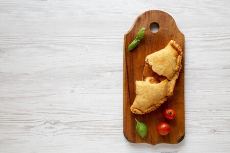 Homemade Deep Fried Italian Panzerotti Calzone with sauce on a rustic wooden board on a white wooden background, top view. Space for text.