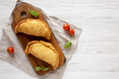 Homemade Deep Fried Italian Panzerotti Calzone on a rustic wooden board on a white wooden table, top view. Flat lay, overhead, from above. Copy space. Stock Photo