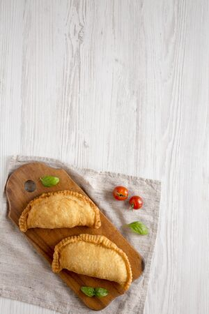 Homemade Deep Fried Italian Panzerotti Calzone on a rustic wooden board on a white wooden table, top view. Flat lay, overhead, from above. Space for text. Stock Photo