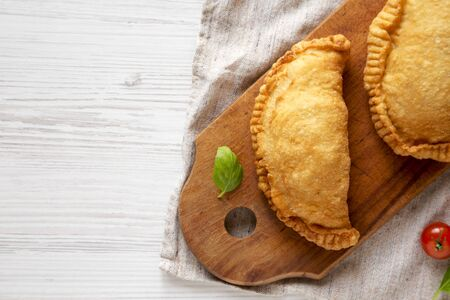 Homemade Deep Fried Italian Panzerotti Calzone on a rustic wooden board on a white wooden background, top view. Flat lay, overhead, from above. Copy space.