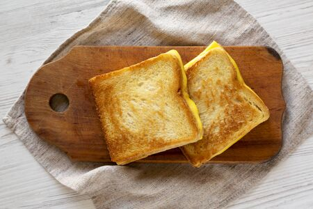 Homemade Grilled Cheese Sandwich on a rustic wooden board on a white wooden background, top view. Overhead, from above, flat lay.