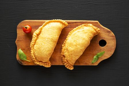 Homemade Deep Fried Italian Panzerotti Calzone on a rustic wooden board on a black background, top view. Flat lay, overhead, from above.