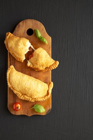 Homemade Deep Fried Italian Panzerotti Calzone with tomato and mozzarella on a rustic wooden board on a black background, top view. Flat lay, overhead, from above. Copy space.