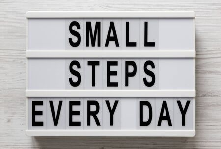 'Small steps every day' words on a lightbox on a white wooden surface, top view. Overhead, from above, flat lay. Close-up. Stock Photo