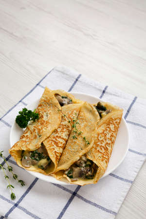Savory Homemade Mushroom, Spinach and Cheese Crepes on a white plate on cloth, low angle view. Copy space. 版權商用圖片
