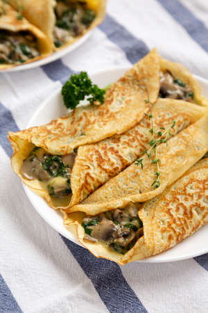 Savory Homemade Mushroom, Spinach and Cheese Crepes on a white plate on cloth, low angle view.
