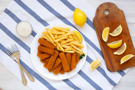 Homemade Fish Sticks and Fries with Tartar Sauce on a white wooden background, top view. Flat lay, overhead, from above.