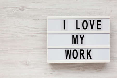 'I love my work' on a lightbox on a white wooden background, top view. Flat lay, from above, overhead. Space for text.
