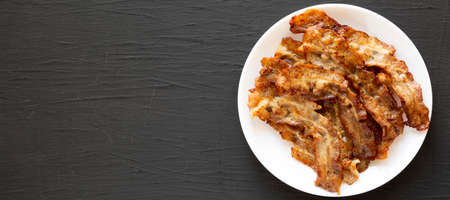 Homemade Fried Bacon on a white plate on a black surface, top view. Overhead, from above, flat lay. Space for text. Standard-Bild