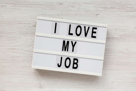 'I love my job' on a lightbox on a white wooden surface, top view. Flat lay, from above, overhead.