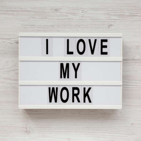 'I love my work' on a lightbox on a white wooden surface, top view. Flat lay, from above, overhead. Standard-Bild