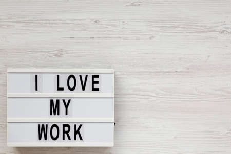 'I love my work' on a lightbox on a white wooden surface, top view. Flat lay, from above, overhead. Space for text. Standard-Bild