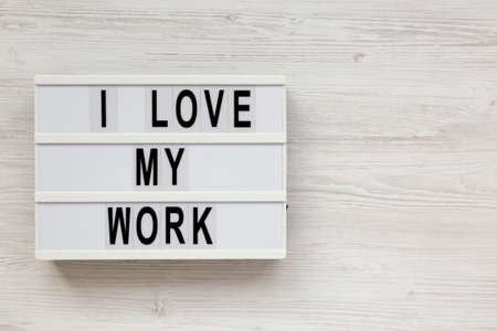 'I love my work' on a lightbox on a white wooden background, top view. Flat lay, from above, overhead. Copy space. Standard-Bild
