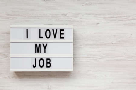 'I love my job' on a lightbox on a white wooden surface, top view. Flat lay, from above, overhead. Copy space.