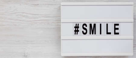 'Smile' word on a lightbox on a white wooden background, top view. Flat lay, from above, overhead. Copy space.