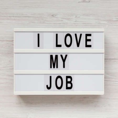 'I love my job' on a lightbox on a white wooden surface, top view. Flat lay, from above, overhead. Close-up.