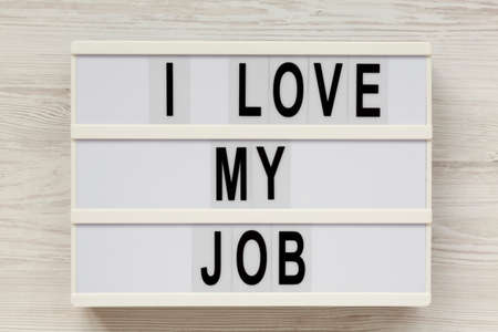 'I love my job' on a modern board on a white wooden background, top view. Flat lay, from above, overhead. Close-up.
