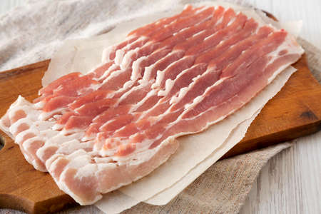 Uncooked Raw Bacon on a rustic wooden board on a white wooden background, side view. Close-up.