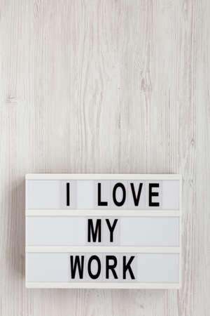 'I love my work' words on a lightbox on a white wooden surface, top view. Flat lay, from above, overhead. Copy space.