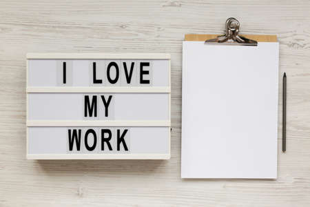 'I love my work' words on a modern board, clipboard with blank sheet of paper on a white wooden background, top view. Flat lay, from above, overhead. Standard-Bild