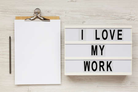 'I love my work' words on a lightbox, clipboard with blank sheet of paper on a white wooden background, top view. Flat lay, from above, overhead.