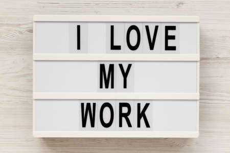 'I love my work' on a lightbox on a white wooden background, top view. Flat lay, from above, overhead.