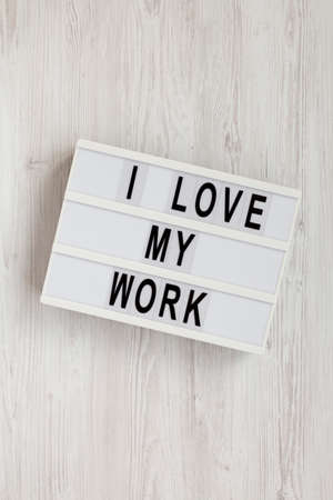 'I love my work' words on a lightbox on a white wooden background, top view. Flat lay, from above, overhead.