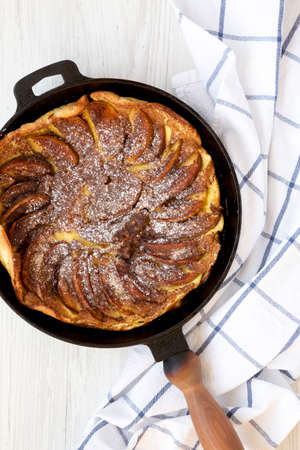 Homemade Apple Dutch Pannekoek Pancake in a cast-iron pan on a white wooden surface, top view. Overhead, from above, flat lay.