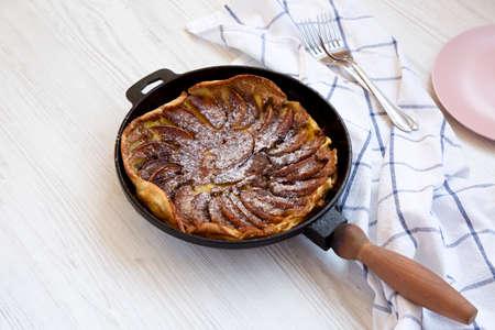 Homemade Apple Dutch Pannekoek Pancake in a cast-iron pan on a white wooden background, side view. Standard-Bild