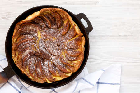 Homemade Apple Dutch Pannekoek Pancake in a cast-iron pan on a white wooden background, top view. Overhead, from above, flat lay. Copy space.