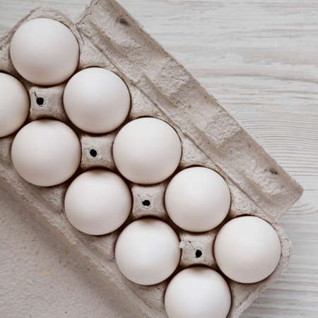 Uncooked Organic White Eggs in a paper box on a white wooden background, top view. Flat lay, overhead, from above.