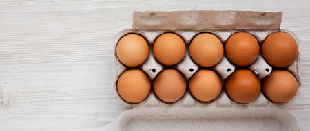 Raw Brown Eggs in a paper box, overhead view. Flat lay, top view, from above. Copy space.