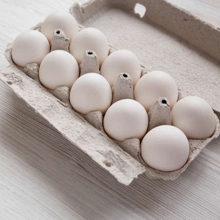 Uncooked Organic White Eggs in a paper box on a white wooden table, side view. Close-up.