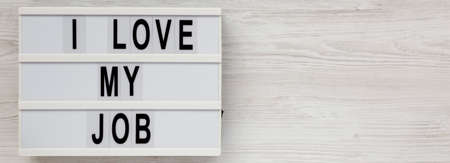 'I love my job' on a lightbox on a white wooden background, top view. Flat lay, from above, overhead. Space for text.