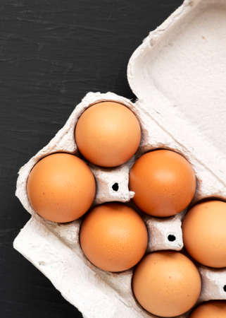 Raw Brown Eggs in a paper box on a black background, top view. Flat lay, overhead, from above.