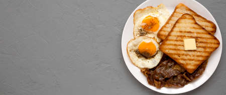 Homemade Healthy Sunnyside Eggs Breakfast on a white plate on a gray surface, top view. Copy space. Standard-Bild