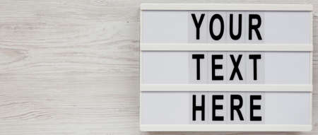 'Your text here' words on a lightbox on a white wooden surface, top view. Flat lay, overhead. Copy space.