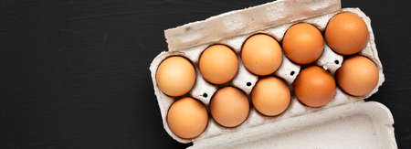 Raw Brown Eggs in a paper box on a black background, top view. Flat lay, overhead, from above. Space for text.