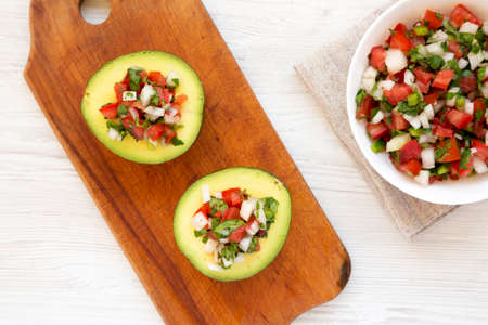 Homemade Pico de Gallo Stuffed Avocado on a rustic wooden board on a white wooden surface, top view. Flat lay, overhead, from above.
