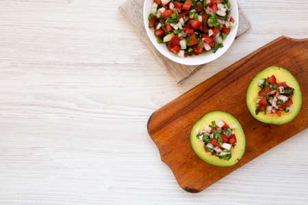Homemade Pico de Gallo Stuffed Avocado on a rustic wooden board on a white wooden background, top view. Flat lay, overhead, from above. Space for text.