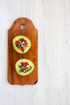 Homemade Pico de Gallo Stuffed Avocado on a rustic wooden board on a white wooden surface, top view. Flat lay, overhead, from above. Space for text. Standard-Bild