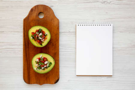 Homemade Pico de Gallo Stuffed Avocado on a rustic wooden board, blank notepad on a white wooden surface, top view. Flat lay, overhead, from above. Space for text.