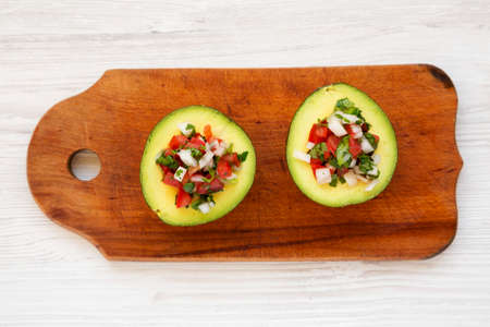 Homemade Pico de Gallo Stuffed Avocado on a rustic wooden board on a white wooden background, top view. Flat lay, overhead, from above.